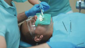 Ο οδοντίατρος μεταχειρίζεται τα δόντια του ασθενή με το οδοντικό τρυπάνι στην κλινική 4K απόθεμα βίντεο