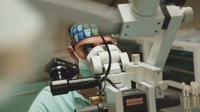 Ο οδοντίατρος χρησιμοποιεί το μικροσκόπιο για την επεξεργασία 4K απόθεμα βίντεο