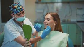 Ο οδοντίατρος παρουσιάζει το αποτέλεσμα οδοντικού καθαρίζοντας το θηλυκό ασθενή του 4K απόθεμα βίντεο
