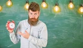 Ο δάσκαλος eyeglasses κρατά το ξυπνητήρι Έννοια πειθαρχίας Άτομο με τη γενειάδα και mustache στην ακριβή στάση προσώπου μέσα στοκ εικόνες