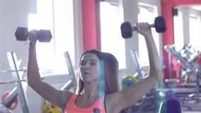 Ο όμορφος καυκάσιος αθλητής κοριτσιών εκτελεί μια άσκηση για τα χέρια στην περιοχή του δελτοειδών μυός και των ώμων φιλμ μικρού μήκους