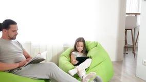 Ο όμορφος καυκάσιος μπαμπάς μαζί με μια χαριτωμένη κόρη κάθεται στην καρέκλα και την κλήση στο skype στον υπολογιστή ταμπλετών Ο  απόθεμα βίντεο