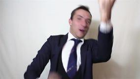 Ο όμορφος νέος επιχειρηματίας εκφράζει ενεργά το χτύπημα χαράς και το δυνατό γέλιο φιλμ μικρού μήκους