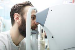 Ο όμορφος νεαρός άνδρας ελέγχει το όραμα ματιών στη σύγχρονη κλινική οφθαλμολογίας Ασθενής στην κλινική οφθαλμολογίας στοκ εικόνα