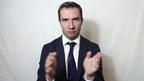 Ο όμορφος νεαρός άνδρας χαμογελά σαρκαστικά και χτυπά τα χέρια του απόθεμα βίντεο