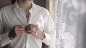 Ο όμορφος νεόνυμφος καθορίζει το πουκάμισό του Γαμήλιο πρωί κίνηση αργή απόθεμα βίντεο