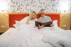 Ο ώριμοι σύζυγος και η σύζυγος εξετάζουν το λεύκωμα στην κρεβατοκάμαρα στοκ φωτογραφίες