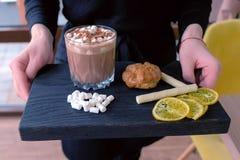 Ο σερβιτόρος φέρνει τη διαταγή στο κακάο πελατών με marshmallow στο γυαλί βράχου που εξυπηρετείται σε έναν ξύλινο μαύρο δίσκο με  στοκ φωτογραφία με δικαίωμα ελεύθερης χρήσης
