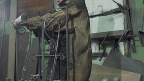 Ο σιδηρουργός ενώνει και στερεώνει τις λεπτομέρειες του σφυρηλατημένου προϊόντος φιλμ μικρού μήκους