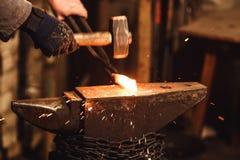 Ο σιδηρουργός που σφυρηλατεί με το χέρι το red-hot μέταλλο στο αμόνι στο σιδηρουργείο με τα πυροτεχνήματα σπινθήρων στοκ φωτογραφία