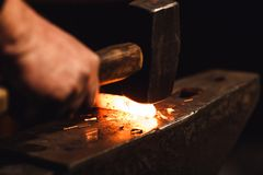 Ο σιδηρουργός που σφυρηλατεί με το χέρι το red-hot μέταλλο στο αμόνι στο σιδηρουργείο με τα πυροτεχνήματα σπινθήρων στοκ φωτογραφίες