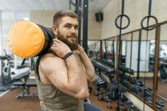 Ο στρατιωτικός αθλητισμός, μυϊκό καυκάσιο γενειοφόρο ενήλικο άτομο που κάνει τις ασκήσεις στη γυμναστική έντυσε σε μια αλεξίσφαιρ στοκ φωτογραφία