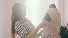 Ο σχεδιαστής μόδας κοριτσιών καρφώνει μια βελόνα στο περιλαίμιο μιας μπλούζας σε ένα μανεκέν, νωρίς το πρωί απόθεμα βίντεο