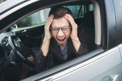 Ο συγκλονισμένος νέος τύπος κάθεται στο αυτοκίνητό του Τα χέρια του είναι στο κεφάλι του, το στόμα του είναι ευρέως ανοικτό ο πον στοκ εικόνες
