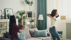 Ο συναισθηματικός σπουδαστής κοριτσιών αφροαμερικάνων χορεύει στο σπίτι γελώντας και έχοντας τη διασκέδαση ενώ ο ασιατικός φίλος  απόθεμα βίντεο