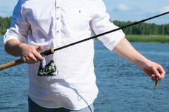 Ο ψαράς σε ένα άσπρο πουκάμισο κρατά μια περιστροφή στην κινηματογράφηση σε πρώτο πλάνο χεριών στοκ εικόνα
