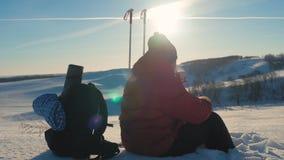 Ο ταξιδιώτης ατόμων κάθεται τη στήριξη σε έναν απότομο βράχο στα χειμερινά βουνά και πίνει το τσάι από thermos οπισθοσκόπες νεολα απόθεμα βίντεο
