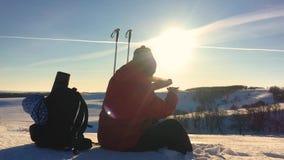 Ο ταξιδιώτης ατόμων κάθεται τη στήριξη σε έναν απότομο βράχο στα χειμερινά βουνά και πίνει το τσάι από thermos οπισθοσκόπες νεολα φιλμ μικρού μήκους