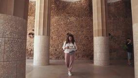 Ο τουρίστας γυναικών περπατά πέρα από το παλαιό ορόσημο και διαβάζει το φυλλάδιο εγγράφου φιλμ μικρού μήκους