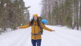 Ο τουρίστας κοριτσιών πηγαίνει σε έναν χειμερινό δασικό δρόμο με ένα σακίδιο πλάτης στους ώμους της φιλμ μικρού μήκους