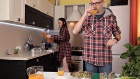 Ο τύπος και το κορίτσι μιλούν στην κουζίνα και το γέλιο ενώ τα τρόφιμα προετοιμάζονται απόθεμα βίντεο