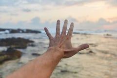 Ο τύπος φτάνει στα σύννεφα Ο τύπος τραβά το χέρι του στη θάλασσα στοκ εικόνα με δικαίωμα ελεύθερης χρήσης