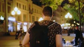 Ο τύπος περπατά στην οδό της στροφής κινηματογραφήσεων σε πρώτο πλάνο πόλεων νύχτας για να εξετάσει τη κάμερα και χαμογελά φιλμ μικρού μήκους