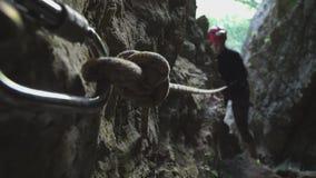 Ο χαμογελώντας αλπινιστής κοριτσιών αναρριχείται σε ένα σχοινί στα βουνά και πλησιάζει τη κάμερα φιλμ μικρού μήκους