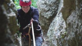 Ο χαμογελώντας αλπινιστής κοριτσιών αναρριχείται σε ένα σχοινί στα βουνά και πλησιάζει τη κάμερα απόθεμα βίντεο