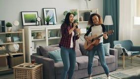 Ο χαρούμενοι νέοι αφροαμερικάνος και Ασιάτης γυναικών στον περιστασιακό ιματισμό παίζουν την κιθάρα, χορεύουν και τραγουδούν στη  απόθεμα βίντεο