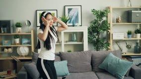 Ο χαρούμενος νέος ευτυχής σπουδαστής γυναικών ακούει τη μουσική μέσω των ακουστικών και χορεύει απολαμβάνοντας το αγαπημένο τραγο φιλμ μικρού μήκους