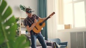Ο χαρούμενος νεαρός άνδρας παίζει την κιθάρα και τραγουδά φορώντας τα γυαλιά εικονικής πραγματικότητας που έχουν τη διασκέδαση στ απόθεμα βίντεο