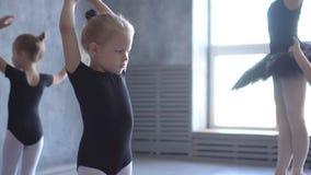 Ο χορευτής κοριτσιών στο σχολείο μπαλέτου μαθαίνει να χορεύει Λίγο Ballerina στην κατάρτιση στο μαύρο χορεύοντας κοστούμι Μπαλέτο φιλμ μικρού μήκους