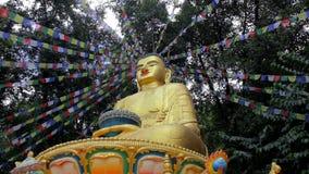 Ο χρυσός Βούδας με τις χρωματισμένες θιβετιανές σημαίες προσευχής στο υπόβαθρο του πράσινου δάσους φιλμ μικρού μήκους