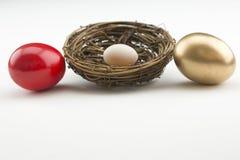 Ο χρυσός, το κόκκινο, και το μικρό αυγό φωλιών είναι σύμβολα επένδυσης στοκ εικόνες