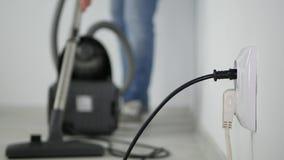 Ο υπάλληλος ατόμων μιας καθαρίζοντας επιχείρησης χρησιμοποιεί μια ηλεκτρική σκούπα στο δωμάτιο γραφείων φιλμ μικρού μήκους