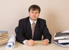 Ο υπάλληλος γραφείων κάθεται στον πίνακα με τους φακέλλους και το σχέδιο στοκ εικόνες