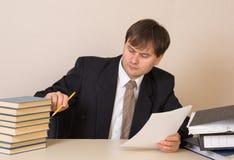 Ο υπάλληλος μετρά τα βιβλία με τα έγγραφα στον πίνακα στο γραφείο στοκ φωτογραφίες