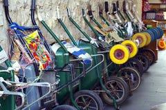 Ο υπόλοιπος κόσμος wheelbarrows ευθυγράμμισε ενάντια σε έναν τοίχο προτού να ανοίξει η αγορά στοκ εικόνα