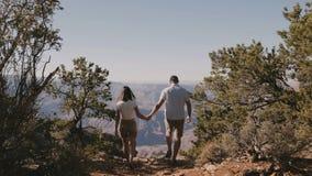 Ο πίσω περίπατος ζευγών άποψης νέος ενήλικος ρομαντικός κρατά μαζί τα χέρια στην επική πανοραμική άποψη του μεγάλου φαραγγιού Αρι φιλμ μικρού μήκους