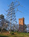Ο παλαιός γοτθικός πύργος κάθεται πίσω από το σύγχρονο πυλώνα ηλεκτρικής ενέργειας στοκ φωτογραφίες με δικαίωμα ελεύθερης χρήσης