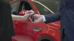 Ο παραγνωρισμένος πωλητής σε ένα επιχειρησιακό κοστούμι δίνει ένα αυτοκίνητο κλειδώνει στην παραγνωρισμένη επιχειρηματία και το κ απόθεμα βίντεο