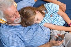 Ο παππούς και η κόρη ακούνε μουσική με το ακουστικό στοκ εικόνα