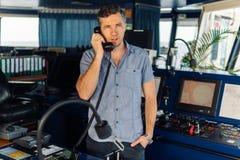 Ο πλοήγησης ανώτερος υπάλληλος υποβάλλει έκθεση από το ραδιόφωνο VHF εν πλω στοκ φωτογραφία με δικαίωμα ελεύθερης χρήσης