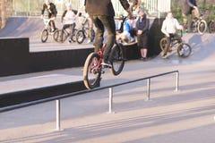 Ο ποδηλάτης BMX κάνει τα τεχνάσματα στις ράγες σε ένα πάρκο σαλαχιών στο υπόβαθρο των ανθρώπων με τα ποδήλατα Άλμα στο bmx στοκ φωτογραφία με δικαίωμα ελεύθερης χρήσης