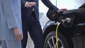 Ο πρεσβύτερος συνδέει το σκοινί δύναμης με ένα ηλεκτρικό αυτοκίνητο Κινήσεις καμερών προς το αριστερό φιλμ μικρού μήκους