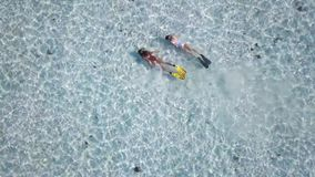 Ο πυροβολισμός από τους τοπ δύο κολυμβητές μελετά το αμμώδες κατώτατο σημείο του ωκεανού γύρω από ένα τροπικό νησί, ηλιόλουστη ημ απόθεμα βίντεο