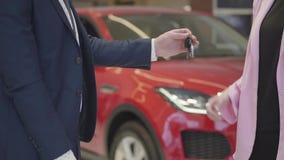 Ο Unrecognizable άνδρας στο κοστούμι δίνει τα κλειδιά στη γυναίκα ρόδινο στενό σε επάνω σακακιών Κόκκινο αυτοκίνητο στο υπόβαθρο  απόθεμα βίντεο