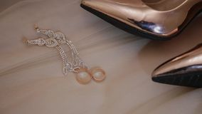 Δαχτυλίδια και κόσμημα παπουτσιών των γαμήλιων χρυσών γυναικών στο κρεβάτι απόθεμα βίντεο