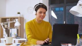 Δημιουργική γυναίκα στα ακουστικά με το lap-top στο γραφείο απόθεμα βίντεο